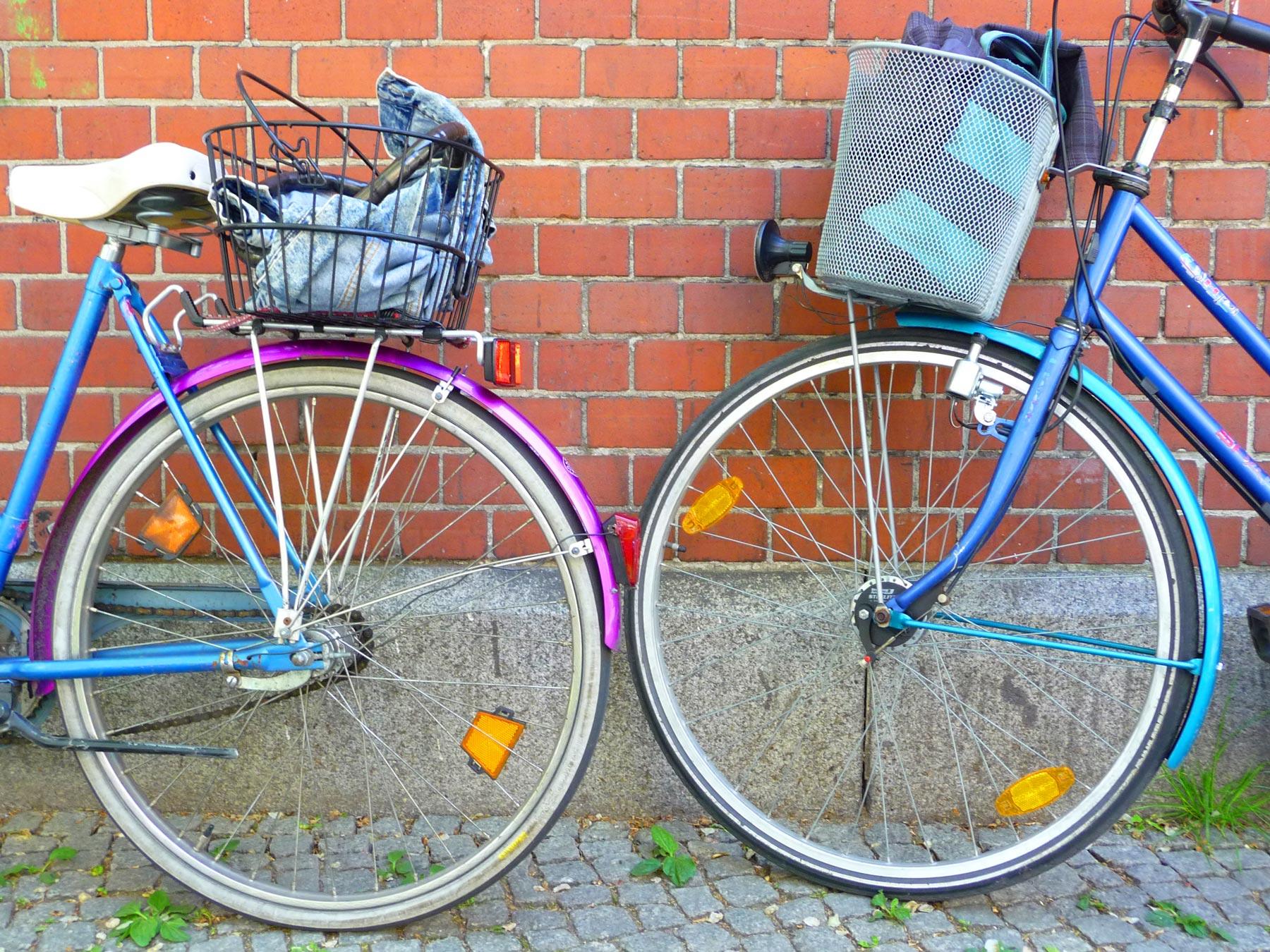 Kaksi pyörää nojaa seinään.