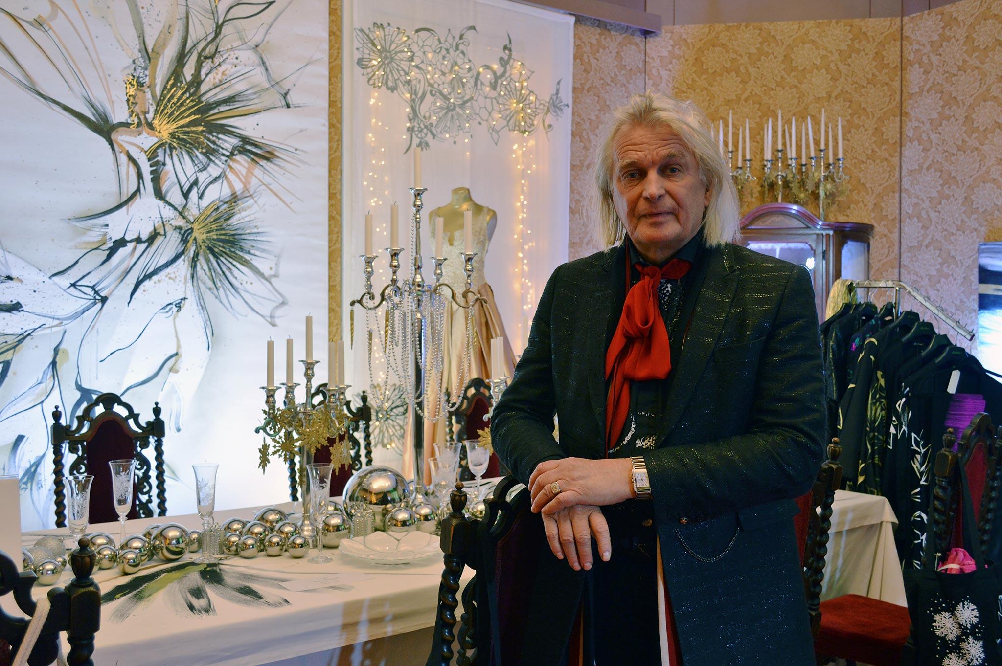 Muotisuunnittelija Jukka Rintala poseeraa ylellisen juhlakattauksensa edessä Aladinin palatsissa. © Elisa Helenius